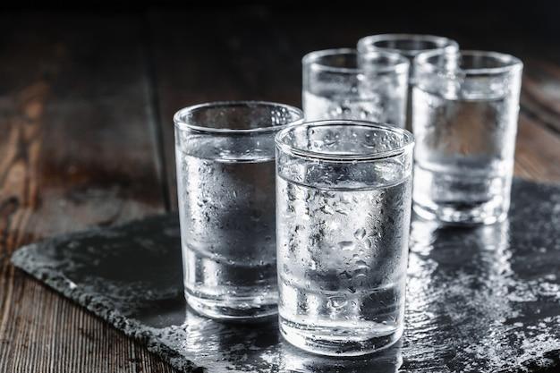 Vodka dans des verres à liqueur sur bois rustique Photo Premium