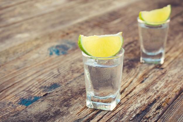 Vodka et tranches de citron vert sur bois Photo Premium