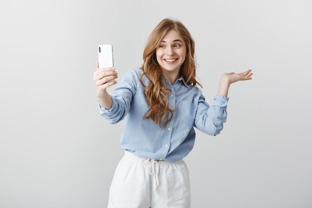 Voici Ma Chambre. Portrait De Femme Heureuse Et Heureuse Excitée En Chemisier Bleu Montrant Autour De Lui Pendant Que Le Chat Vidéo Via Smartphone, Souriant Largement, Dirigeant à L'espace De Copie Sur Un Mur Gris Photo gratuit