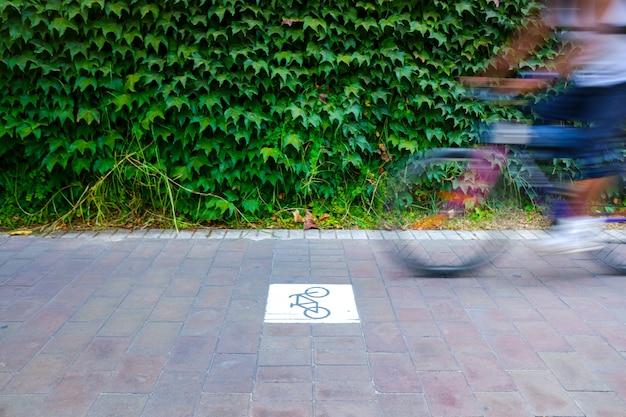 Voie cyclable séparée du trafic avec signal, motard flou. Photo Premium