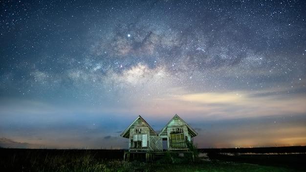 Voie lactée, galaxie et maisons jumelles du village de pakpra, province de phattalung, thaïlande Photo Premium