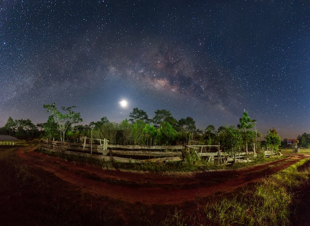 Voie lactée et pleine lune sur un chemin de terre en campagne Photo Premium