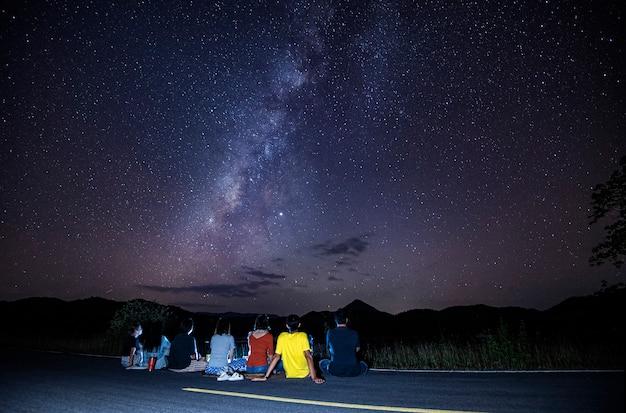 Voie lactée avec les touristes assis sur la route en regardant la nuit du ciel Photo Premium