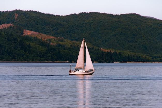 Voilier Naviguant Dans Une Belle Rivière Avec Une Forêt Sur Une Colline Escarpée Photo gratuit