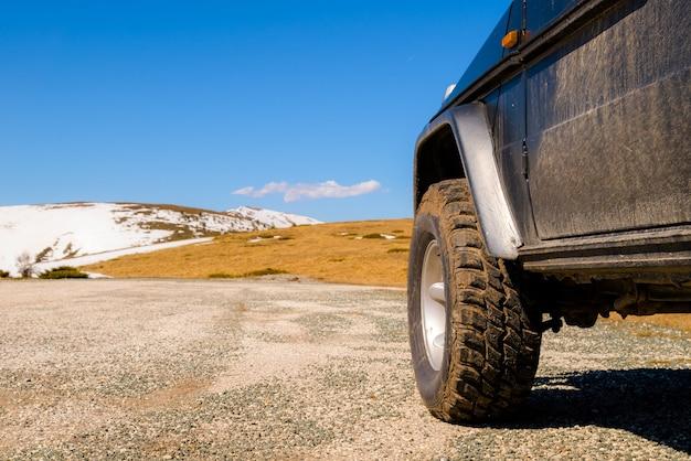 Voiture 4x4 Hors Route Dans Les Montagnes Enneigées Par Une Journée Ensoleillée. Photo Premium