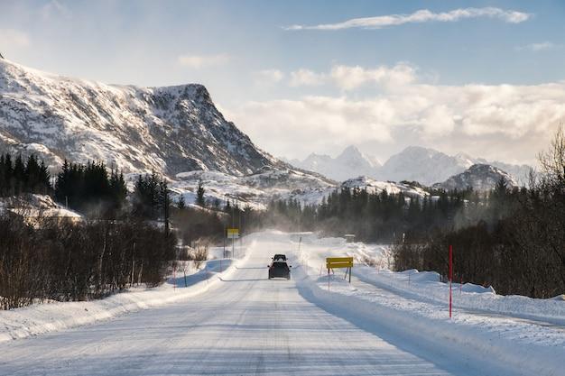 Voiture, conduite, sur, route neigeuse, à, chaîne de montagnes Photo Premium