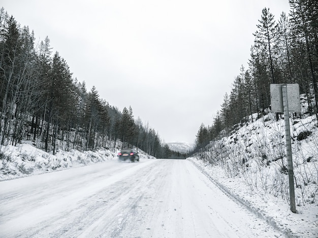 La Voiture Est En Mouvement. Montée Raide Et Glissante. Route D'hiver Glissante Photo Premium