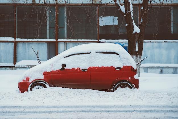 La voiture garée se dresse le long de la route tout en neige Photo Premium