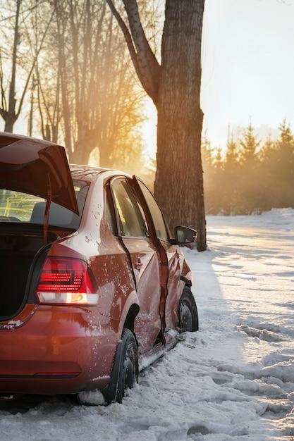 Voiture Et Glace Sur La Route D'hiver. La Voiture A Eu Un Accident En Hiver, S'est écrasée Dans Un Arbre Et S'est Glissée Dans Un Fossé Sur Le Bord De La Route. Photo Premium