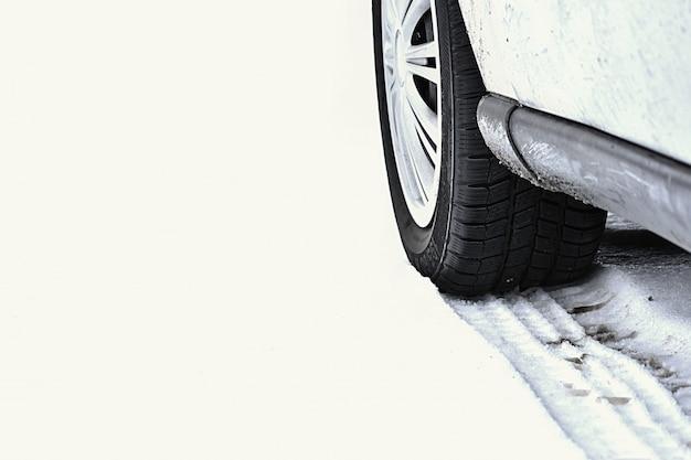 Voiture en hiver tire sur une route enneigée par mauvais temps. Photo gratuit