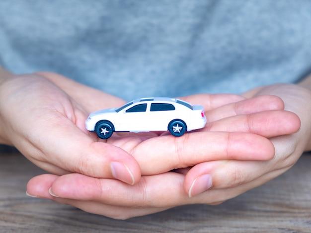 Voiture de jouet blanche dans les mains des femmes Photo Premium