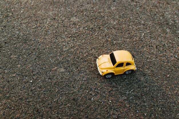 Voiture jouet jaune sur la plage au soleil en été. Photo Premium