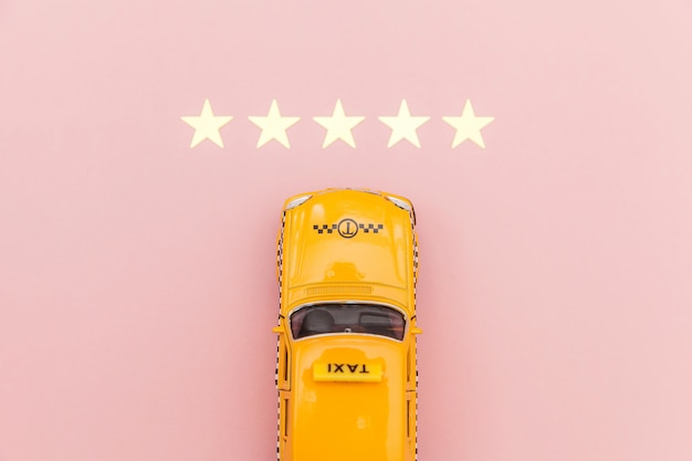 Voiture Jouet Jaune Taxi Cab Et Cote 5 étoiles Isolé Sur Fond Rose. Application Téléphonique Du Service De Taxi Pour La Recherche En Ligne D'appels Et De Réservation De Cabine. Symbole De Taxi. Copiez L'espace. Photo Premium