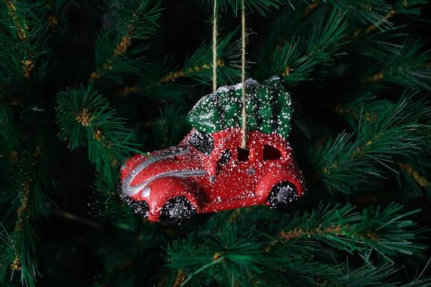 Voiture De Jouet De Noël Rouge Sur L'arbre Du Nouvel An. Composition De Noël. Photo Premium