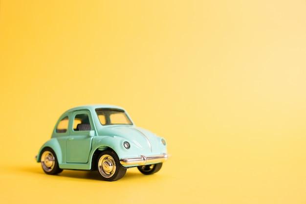 Voiture de jouet rétro bleu sur jaune. concept de voyage d'été. taxi Photo Premium