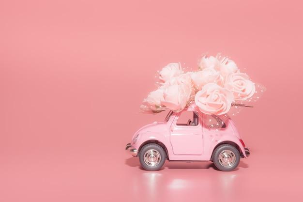 Voiture jouet rétro rose avec bouquet de roses blanches sur fond rose Photo Premium