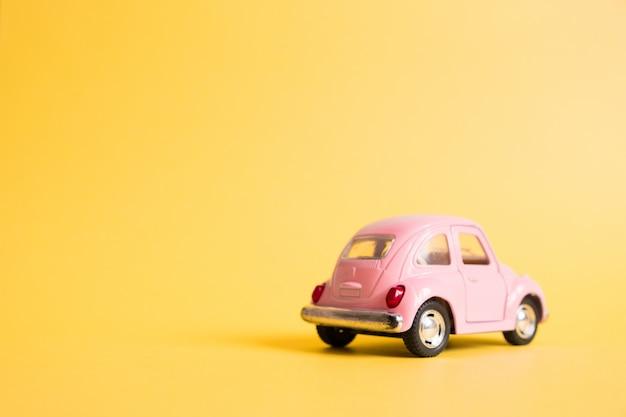 Voiture jouet rétro rose sur jaune. concept de voyage d'été. taxi. Photo Premium