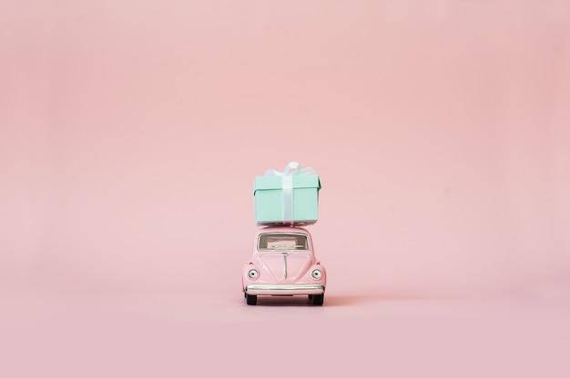 Voiture jouet rose modèle rétro offrant une boîte cadeau sur fond rose Photo Premium