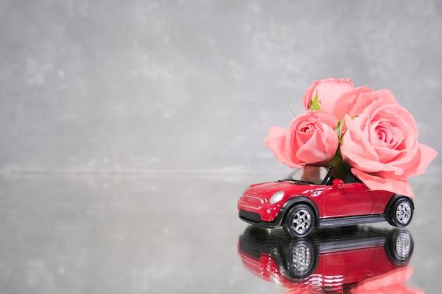Voiture jouet rouge offrant un bouquet de fleurs roses roses sur fond gris. Photo Premium