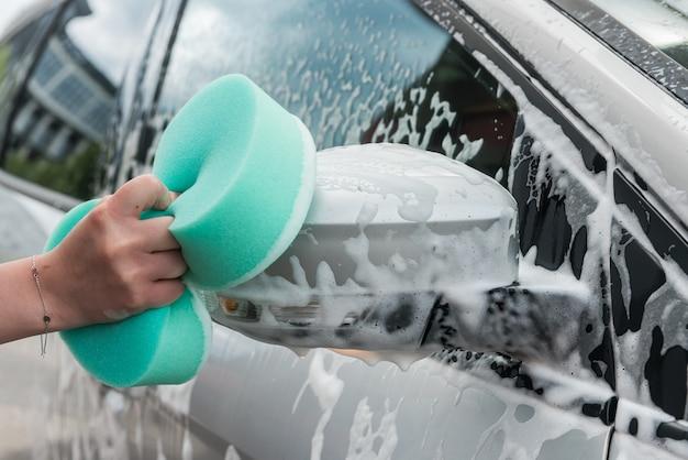 Voiture De Nettoyage Des Mains Des Femmes En Service Avec De L'eau Et De La Mousse De Savon. Lavage Automatique Photo Premium