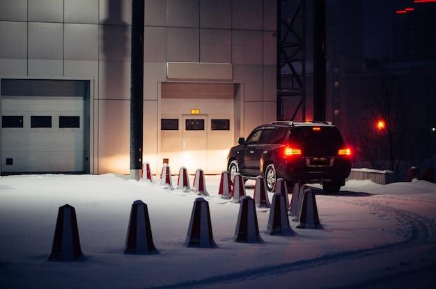 La voiture noire hors route appelle dans le portail automatique pour l'entretien le soir d'hiver Photo Premium