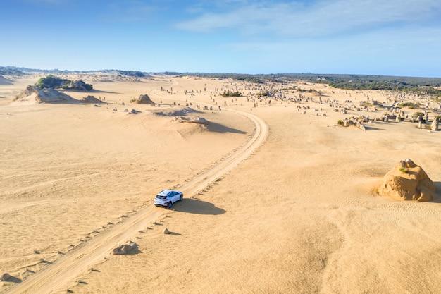 Voiture à quatre roues motrices sur pinnacles drive, chemin de terre dans le désert de pinnacles, australie-occidentale. Photo Premium