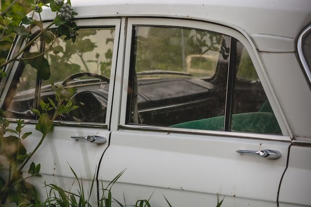 Voiture rétro blanche sur le côté dans l'herbe. porte de voiture. Photo Premium