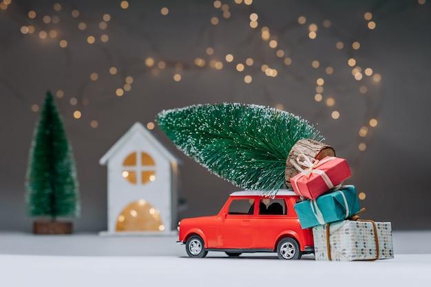 Voiture Rouge Avec Un Arbre De Noël Sur Le Toit. Dans Le Contexte De La Maison. Concept Sur Le Thème De Noël Et Du Nouvel An. Photo Premium