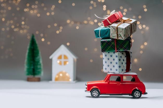 Voiture Rouge Avec Des Cadeaux Sur Le Toit. Dans Le Contexte De La Maison Et De L'arbre. Concept Sur Le Thème De Noël Et Du Nouvel An. Photo Premium