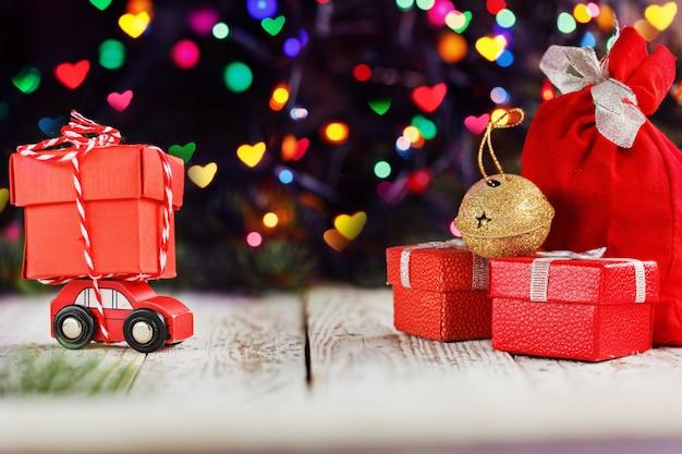 Voiture rouge miniature transportant une grosse boîte rouge. concept de vacances joyeux noël. Photo Premium