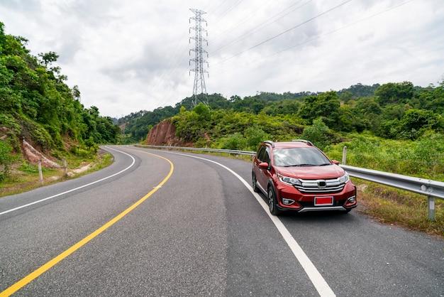 Voiture rouge de suv sur route asphaltée avec forêt verte de montagne Photo Premium