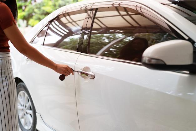 La voiture se déverrouille, la femme utilise une clé pour ouvrir la portière de la voiture Photo Premium