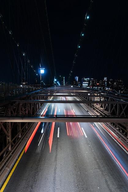 Voitures sur le pont avec le flou de mouvement la nuit Photo gratuit