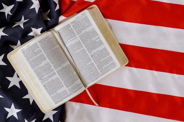 Volant De Drapeau Américain Avec Open Est En Train De Lire Le Livre De La Sainte Bible Avec La Prière Pour L'amérique Sur Le Drapeau Américain Photo Premium