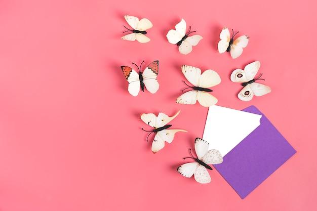 Une volée de papillons chou s'envoler de l'enveloppe violette sur fond rose Photo Premium