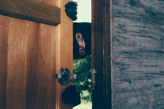 Le voleur est apparu à la porte de la maison. Photo gratuit