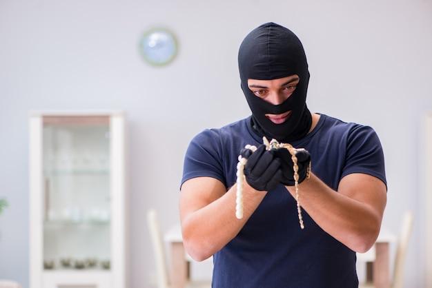 Un voleur portant une cagoule vole des objets de valeur Photo Premium