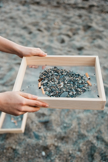 Volontaire collecte de cigarettes à la plage Photo gratuit