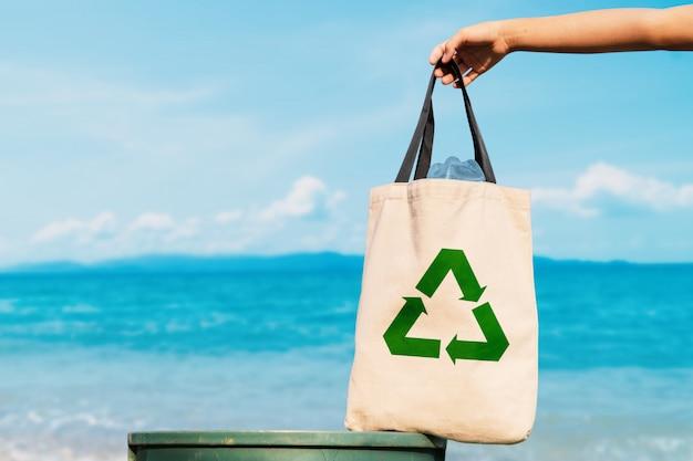 Le volontaire tenant un sac en plastique dans une poubelle Photo Premium