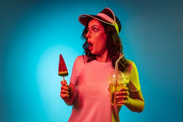 Vous Vous Demandez Jeune Femme Dans Une Casquette Tenant Des Bonbons Et Des Boissons Sur Studio Néon Bleu Branché Photo gratuit