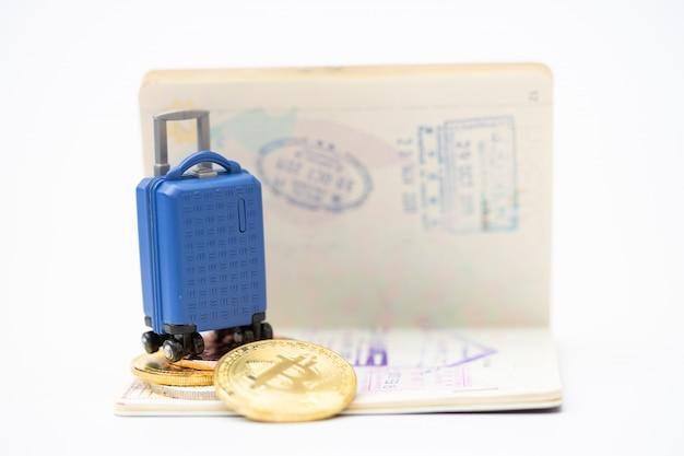 Voyage et épargne financière. bagages miniatures et modèle de pièce de monnaie sur le passeport. payer avec le concept de pièce de monnaie. Photo Premium