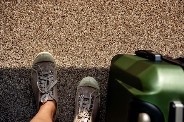 Voyage en été concept. vue de dessus du jeune voyageur sur des chaussures de baskets avec bagages Photo Premium