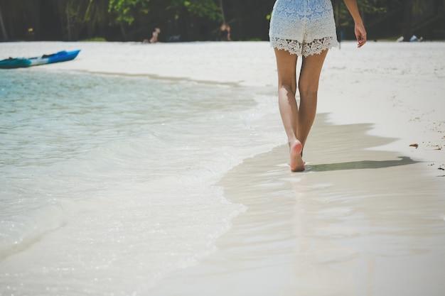 Voyage femme pied sur plage Photo Premium