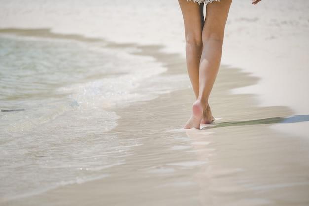 Voyage femme pied sur la plage Photo Premium