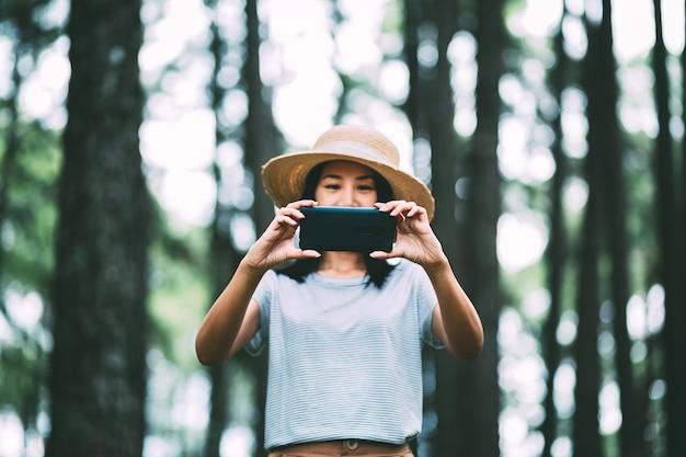 Voyage D'hiver Se Détendre Concept De Vacances, Jeune Femme Asiatique De Voyageur Heureux Avec Téléphone Mobile Visites Dans La Forêt De Pins à Suan Son Bo Kaeo Park, Chiang Mai, Thaïlande Photo Premium