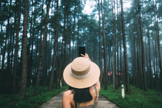 Voyage D'hiver Se Détendre Concept De Vacances, Jeune Femme Asiatique De Voyageur Heureux Avec Téléphone Mobile Visites Dans Le Jardin De Pins à Doi Bo Luang Forest Park, Chiang Mai, Thaïlande Photo Premium