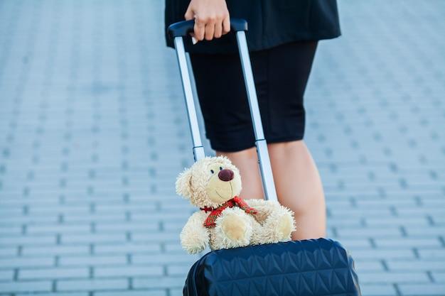 Voyage. jeune femme occasionnelle recadrée va à l'aéroport à la fenêtre avec valise attendant l'avion Photo Premium