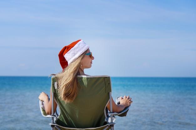 Voyage Le Réveillon Du Nouvel An Sur La Plage Par La Fille De La Mer En Chapeau De Noël Se Fait Bronzer Au Soleil Femme Photo Premium