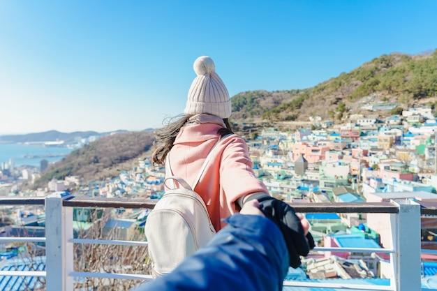 Voyager ensemble. suivez-moi, jeune femme menant un petit ami dans le village culturel gamcheon situé à busan, en corée du sud. Photo Premium