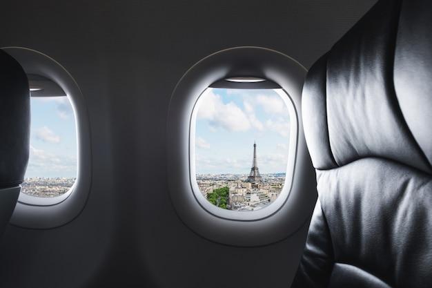 Voyager à paris, en france, monument célèbre et destination de voyage en europe. vue aérienne de la tour eiffel à travers la fenêtre de l'avion Photo Premium